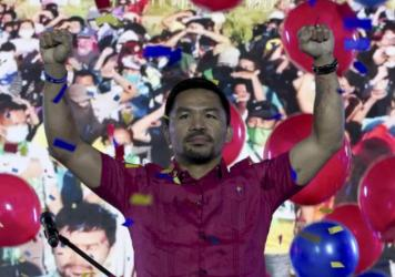 In this photo provided by the Manny Pacquiao MediaComms, Senator Manny Pacquiao raises his hands during a national convention of his PDP-Laban party in Quezon city, Philippines on Sunday Sept. 19, 2021. Philippine boxing icon and senator Manny Pacquiao s
