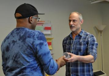 At the San Francisco AIDS Foundation, staff members Tyrone Clifford (left) and Rick Andrews (right) demonstrate how a contingency management visit typically begins, with a participant picking up a specimen cup for a urine sample. If the sample tests nega