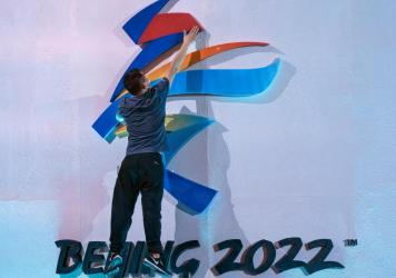 A crew member leaps to fix a logo for the 2022 Winter Olympics in Beijing earlier this month. The International Olympic Committee says it will allow fans from mainland China to attend the competition in person.