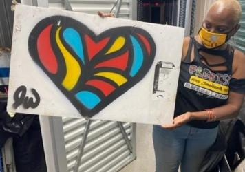 Nadine Seiler poses with a piece of artwork that was once displayed on the fence outside the White House. Seiler is working to find new homes for the 700+ signs/artifacts.