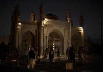 """Taliban fighters walk at the entrance of the Eidgah Mosque after an explosion in Kabul, Afghanistan, Sunday, Oct. 3, 2021. The attack left a """"number of civilians dead,"""" a Taliban spokesman said."""
