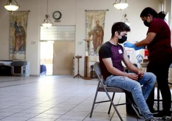 A person receives the Pfizer COVID-19 vaccine at a clinic at St. Patrick's Catholic Church in Los Angeles in April.