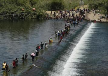 In this Sept. 18, 2021, file photo Haitian migrants use a dam to cross into the United States from Mexico in Del Rio, Texas.