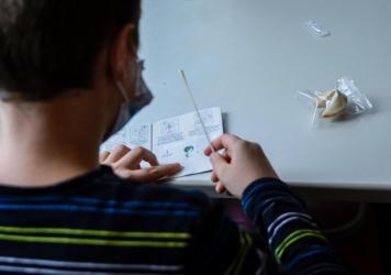 A pupil wearing a face mask reads instructions for a coronavirus rapid test kit at the start of a lesson at an elementary school in Berlin on August 9, 2021.