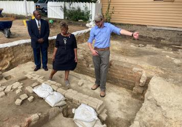Reginald F. Davis, from left, pastor of First Baptist Church in Williamsburg, Connie Matthews Harshaw, a member of First Baptist, and Jack Gary, Colonial Williamsburg's director of archaeology, stand at the brick-and-mortar foundation of one the oldest B