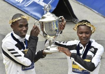 Benson Kipruto (L) and Diana Kipyogei (R) of Kenya hold up the victory trophy after taking first place in the professional men's and women's divisions during the 125th Boston Marathon in Boston, Massachusetts on Monday. The first Boston Marathon since Ap