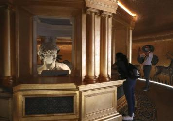 In this Friday, Oct. 1, 2021 file photo, visitors take photos of the 3D re-production of Michelangelo's David at the Italy's pavilion at the Dubai Expo 2020 in Dubai, United Arab Emirates. One of the most talked about attractions at the world's fair unde