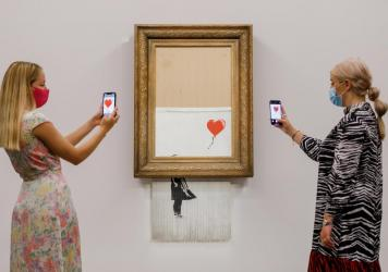 """Banksy's """"Love is in the Bin"""" (2018) is installed at Sotheby's on September 03, 2021 in London, England."""