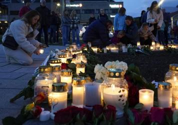 Flowers and candles are placed at the scene of an attack on the square, in Kongsberg, Norway, Thursday. Norwegian authorities say the bow-and-arrow rampage by a man who killed five people in a small town appeared to be a terrorist act. Police identified