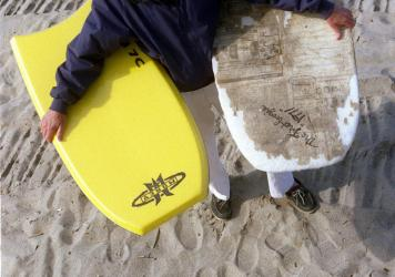 Tom Morey, inventor of the Boogie Board, is photographed on Capistrano Beach holding a newer model (left) and (right) his original 1971 Boogie Board.