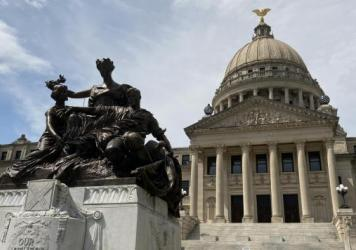 A monument to the women of the Confederacy stands in front of the Mississippi State Capitol.