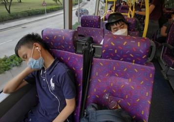 Passengers sleep on the upper deck of a double-decker bus in Hong Kong on Saturday.