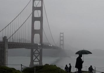 A pedestrian walks with an umbrella near the Golden Gate Bridge in San Francisco during a shower on Wednesday. Strong storms are expected to bring substantial rain to the Western U.S. within the next week.