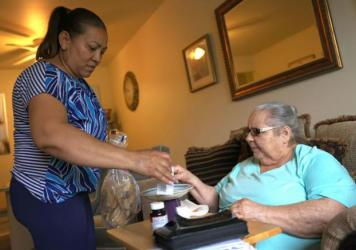 Expanded funds for in-home care can help seniors and disabled Americans stay in their homes. Here, Lidia Vilorio, a home health aide, gives her patient Martina Negron her medicine and crackers for her tea in May in Haverstraw, N.Y.