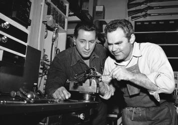 In this photo from a Hollywood studio gun department in 1958, Rodd Redwing (left) checks the final adjustment that Bob Lane is making on a six-gun. Redwing is an actor and a teacher of western gun handling. Lane is one of the men who repair and service t