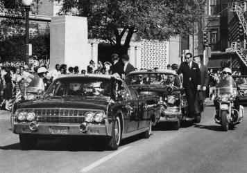 In this Nov. 22, 1963, file photo, seen through the foreground convertible's windshield, President John F. Kennedy's hand reaches toward his head within seconds of being fatally shot. About 90% of the government records surrounding the assassination have