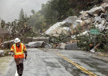 Caltrans maintenance supervisor Matt Martin walks by a landslide covering Highway 70 in the Dixie Fire zone on Sunday in Plumas County, Calif. Heavy rains blanketing Northern California created slide and flood hazards in land scorched during last summer'