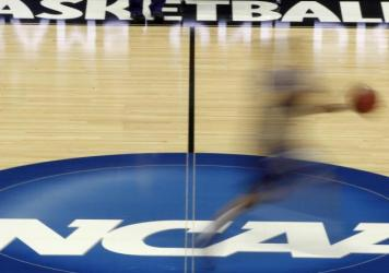 A player streaks across the NCAA logo at midcourt during basketball practice in this file photo from March 14, 2012.