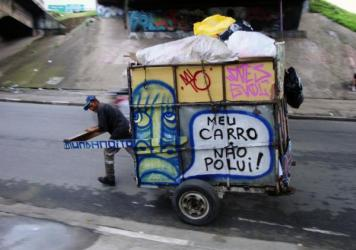 """Trash pickers collect 90 percent of waste that gets recycled in Brazil yet local governments give them little support. The message on this cart: """"One <em>catadore</em> does more than an environmental minister."""""""