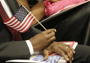 A new U.S. citizen holds an American flag during a naturalization ceremony in July. An Arizona law will require graduating high school seniors to pass the same civics test given to candidates for U.S. citizenship.