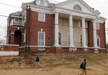 """Students walk past the Phi Kappa Psi fraternity house on the University of Virginia campus on December 6, 2014 in Charlottesville, Va. The fraternity was at the center of an explosive <em>Rolling Stone </em>article that the magazine later <a href=""""http:/"""