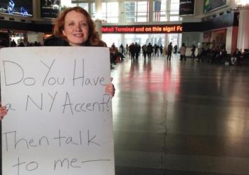 Heather Quinlan searched for New York accents around the city for her documentary <em>If These Knishes Could Talk</em>. She holds up a sign at the Whitehall Ferry Terminal in Manhattan.