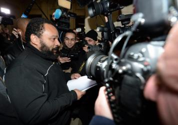 "French comedian Dieudonne M'Bala M'Bala arrives for his trial at the courthouse in Paris on Jan. 28. He goes on trial again today on charges of ""defending terrorism,"" following remarks he made on Facebook after the deadly attack on the satirical weekly <"
