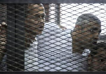 Australian journalist Peter Greste (left) of Al-Jazeera news channel and his colleagues, Egyptian-Canadian Mohamed Fadel Fahmy (center) and Egyptian Baher Mohamed, listen to the verdict inside the defendants' cage during their trial for allegedly support