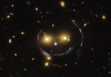 An image taken with the NASA/ESA Hubble Space Telescope of the galaxy cluster SDSS J1038+4849 shows that it seems to be smiling. The space agency says it's the result of a symmetrical alignment of the galaxy cluster and the telescope — along with a pow