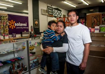 Diego Lobaton stands with his mother, Hedy Julca, and her son, Bruce, inside their cellphone store. Lobaton, Julca and Lobaton's brother Luis were arrested last year after San Diego police stopped the brothers on the suspicion they were breaking into the