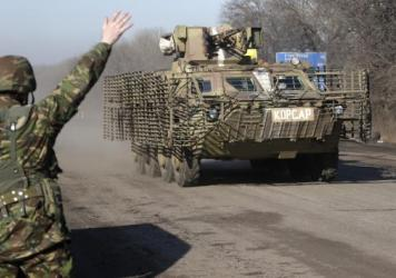 A Ukrainian government soldier waves to an armored vehicle on a road near the town of Artemivsk, Ukraine, Friday. Fighting between Russia-backed separatists and Ukrainian government forces has continued despite the agreement reached by leaders of Russia,
