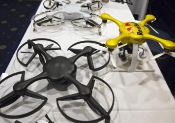 Drones are displayed at an event with the Small Unmanned Aerial Vehicles (UAV) Coalition, last month. The FAA's proposed new rules for their commercial use require certified pilots to fly them and limit their speed, altitude and area of operation.