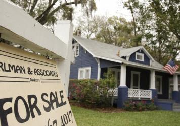 A realty sign hangs in front of a home for sale in Orlando, Fla. Housing advocates say banks, stung by the housing crisis and its fallout, remain reluctant to lend.