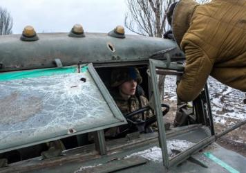 Ukrainian soldiers repair their truck's bullet-shattered windshield Thursday, hit during their withdrawal from Debaltseve Wednesday.