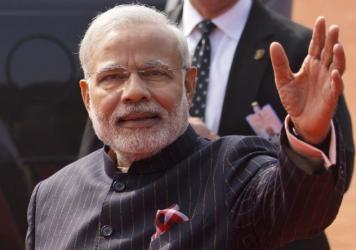 Indian Prime Minister Narendra Modi wears a dark pinstriped suit with his name monogrammed in dull gold stripes Jan. 25 during a reception for U.S. President Obama in New Delhi, India. The suit was auctioned off Friday for more than 43 million rupees, or about $694,000.