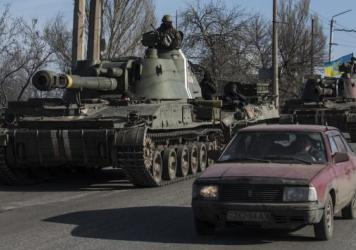 Ukrainian troops ride on self-propelled artillery near Artemivsk, eastern Ukraine, Monday. A Ukrainian military spokesman says that separatist attacks are delaying Ukrainian forces' pullback of heavy weapons from the front line.