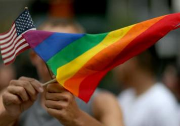 A protester waves an American flag and a rainbow flag in support of gay marriage in Miami in 2014. Secretary of State John Kerry announced Tuesday the appointment of a special envoy for the human rights of LGBT persons.
