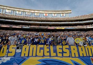 "Fans hold a ""Los Angeles Rams"" sign during a San Diego Chargers game against the St. Louis Rams last year. Both teams are part of proposals to build new NFL stadiums in the LA area."
