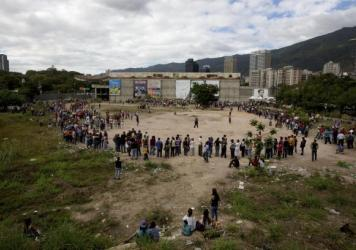 People line up outside the Bicentenario, a state-run supermarket, in Caracas, Venezuela, on Jan. 9. Most of the shortages in Venezuela are driven in part by the country's tight currency controls, which make it hard to get dollars at a subsidized rate for