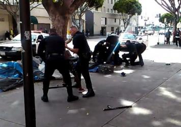A cellphone video captured the deadly struggle between Los Angeles police officers and a man on a city sidewalk (in background). Seconds after this image appears in the video, shots were fired that killed the man, a robbery suspect.