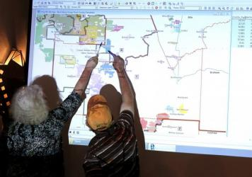 Arizona commission attorney Mary O'Grady (left) and Stephen Miller, a city council member, point to a possible redistricted map in 2011.