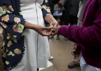 Tori Sisson, left, and Shante Wolfe, right, exchange wedding rings during their ceremony, Feb. 9, 2015, in Montgomery, Ala. They were the first couple to file their marriage license in Montgomery County. Such marriage licenses appear to be on hold again following a state Supreme Court ruling on Tuesday.