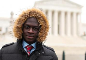 """Tarkpor Mambia on his trip to Washington, D.C., this month (that's the Supreme Court behind him). He says he """"literally froze"""" during his first American winter in 2013 but is getting used to the cold weather."""