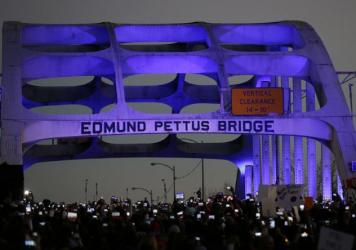 In this Sunday, Jan. 18, 2015, photo, marchers hold up cellular phones to record the rapper Common and singer-songwriter John Legend performing at the foot of the Edmund Pettus Bridge.