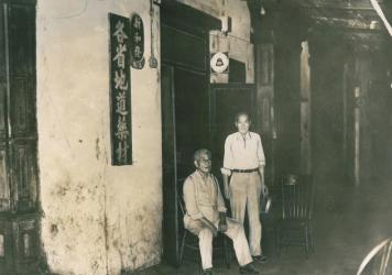 Chinese who operated small shops in New Orleans' Chinatown for many decades learned in 1937 that their small city-within-a-city was doomed to make way for a parking lot. Shown in front of one of the shops on Tulane Avenue between Elk Place and Rampart Street are Big Gee, seated, and Lee Sing, standing.