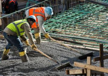 """Construction workers in Washington, D.C., in December. The latest jobs report will further drive the """"misery index"""" to its lowest level in more than half a century. But economists say meager wages and big debts are still problems."""