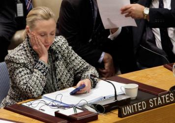 U.S. Secretary of State Hillary Rodham Clinton checks her mobile phone in March 2012 after her address to the Security Council at United Nations headquarters. While she's asked the State Department to quickly release her emails from her tenure as secretary, the process likely will take months — dragging out media coverage and critical questions.