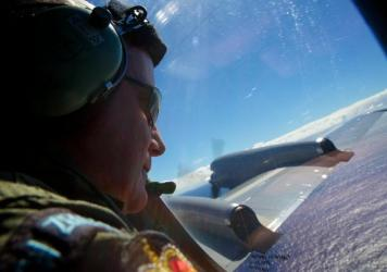 Sgt. Trent Wyatt, a crew member of a Royal New Zealand Air Force P-3 Orion, looks out in the search for MH370 over the Indian Ocean in April of last year. A Malaysian official says the search will continue through the end of May 2015, but if nothing is f