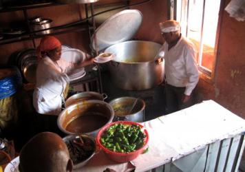 Customers line up, waiting to order from Chef Chane in Addis Ababa, Ethiopia. He runs his restaurant like a fiefdom, dispensing food and insults majestically from the kitchen, which doubles as a serving station.