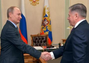 Russian President Vladimir Putin (left) greets Supreme Court Chairman Vyacheslav Lebedev. The Kremlin says Putin, who has been out of public view for more than a week, is perfectly healthy.
